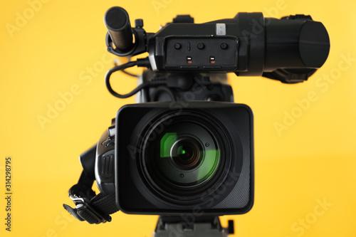 Obraz na plátně Modern professional video camera on yellow background, closeup