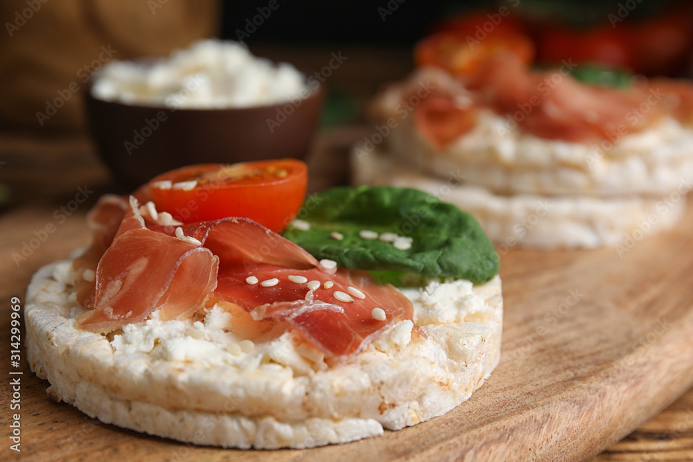 Fototapeta Puffed rice cake with prosciutto, tomato and basil on wooden board, closeup