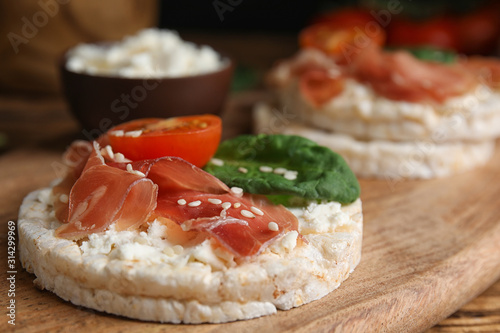 Obraz Puffed rice cake with prosciutto, tomato and basil on wooden board, closeup - fototapety do salonu