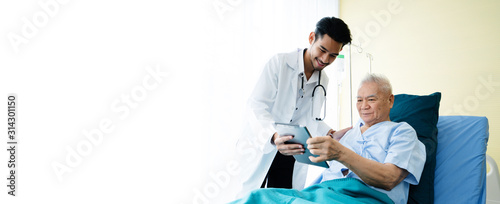 Obraz Asian man doctor uses a tablet to explain the treatment of senior male patients lying in hospital beds. Modern medical care Use technology to treat Concept of looking after elderly and retirees - fototapety do salonu