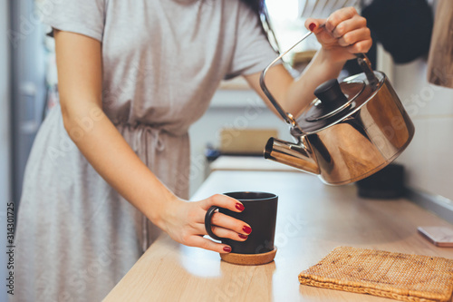 Obraz woman in kitchen drinking coffee or tea - fototapety do salonu