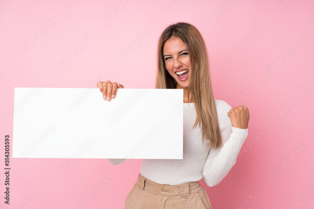 Fototapeta Young blonde woman over isolated pink background holding an empty white placard for insert a concept