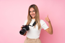 Young Blonde Woman Over Isolated Pink Background With A Professional Camera And With Thumb Up