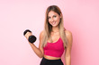 Young sport blonde woman over isolated pink background making weightlifting with kettlebell