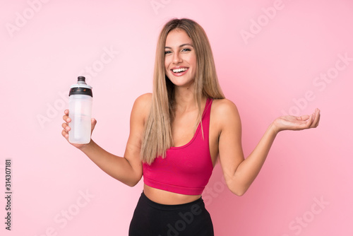 Fototapeta Young sport blonde woman over isolated pink background with sports water bottle obraz