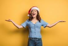 Excited Girl In Santa Hat Laughing With Open Arms On Yellow Background