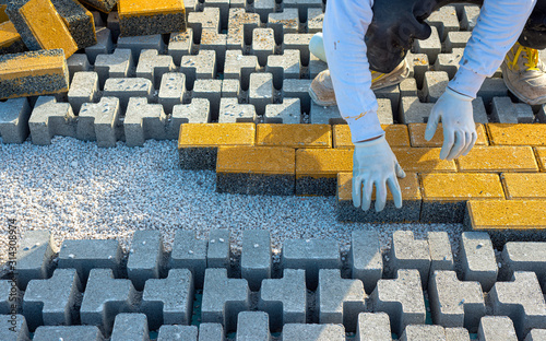 Fotografie, Obraz Paving stone worker is putting down pavers during a construction of a city street