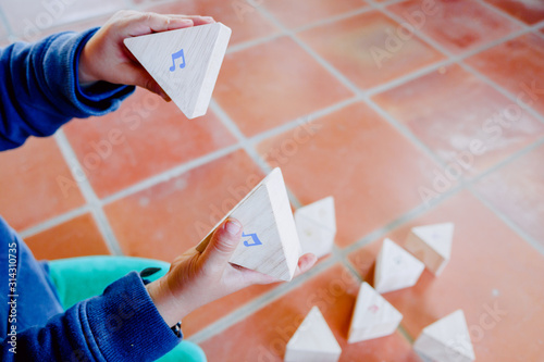 Fotografie, Tablou  Child holding some wooden blocks with musical notes to learn music theory