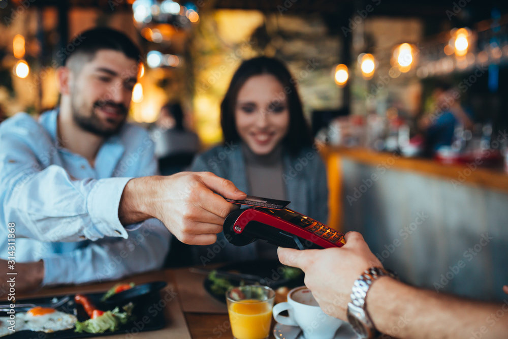 Fototapeta man paying with credit card in restaurant