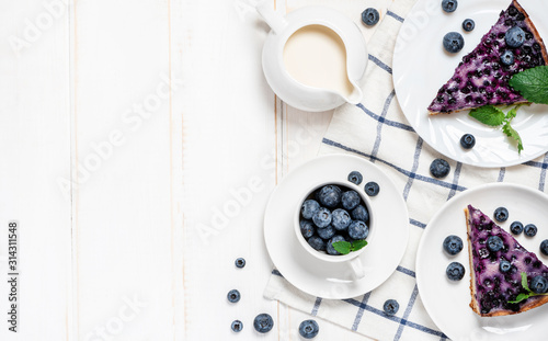 Obraz na plátne Pieces of blueberry pie and blueberries lie in white plates on the table, top view, copy space