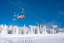 Skiers On Chairlift At Mountain Ski Resort With Snowy Trees In The Background