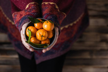 Woman In A Huge Winter Sweater Sits On The Wooden Rustic Floor With Small Iron Bucket Of Tangerines (mandarin).