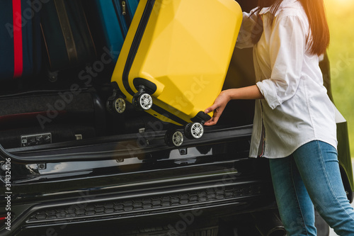 Stampa su Tela Asian woman lifting yellow suitcase into SUV car during travel in long weekend trip
