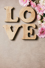 Word LOVE From Oak Wooden Letters With Variety Of Pink Roses Flowers Over Brown Texture Background. Flat Lay, Space. St. Valentines Greeting Card