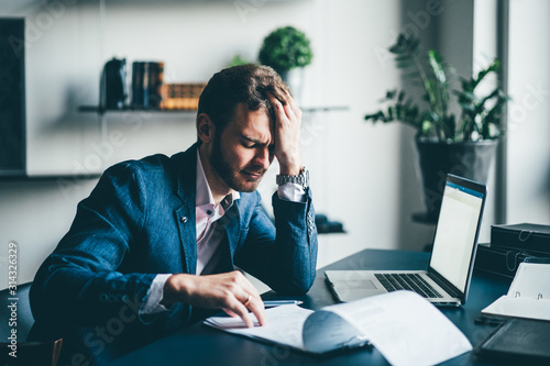 Fototapety, obrazy: Manager sitting at the desk with laptop