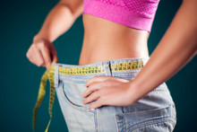Woman Wearing Big Size Jeans With Meter On The Belt. Weight Loss And Diet Concept
