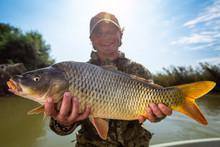 Happy Fisherman Holds The Big Carp Fish (Cyprinus Carpio) And Smiles