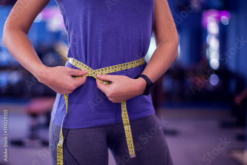 Woman measuring waist with meter in the gym Fototapeta