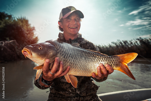 Obraz Happy young fisherman holds the big Carp fish (Cyprinus carpio) and smiles - fototapety do salonu
