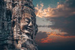 canvas print picture - The Bayon - Khmer temple at Angkor Wat in Cambodia. Popular tourist attraction. Smiling stone faces on the towers of temple. Dramatic sky.