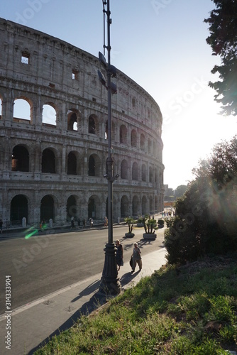 Sun setting behind the Colosseum in Rome, Italy in the warm days of the summer months