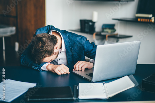 Obraz Sad businessman sitting at his desk. - fototapety do salonu