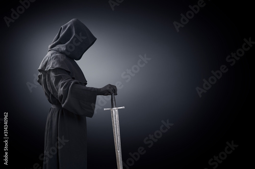 Foto Ghostly figure with medieval sword in the dark
