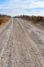 Dirt Road In A Desert Landscap...