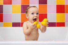 Baby In Bathtub Holding Rubber Ducks With Funny Excited Expression