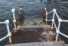 Concrete Staircase With White Metal Barriers Sinking Into The Water