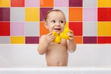 Happy Baby In Bathtub Holding Rubber Ducks