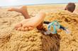 Leinwanddruck Bild - Snorkel, mask and boy feet buried in sand beach
