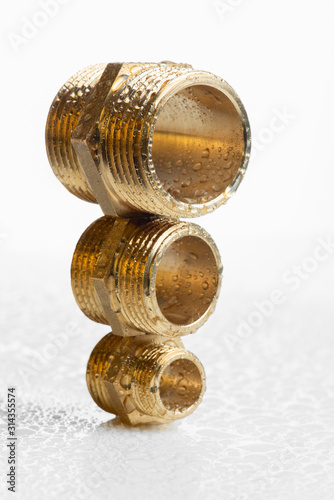 Leinwand Poster Closeup brass pipe fitting on white wet workshop table