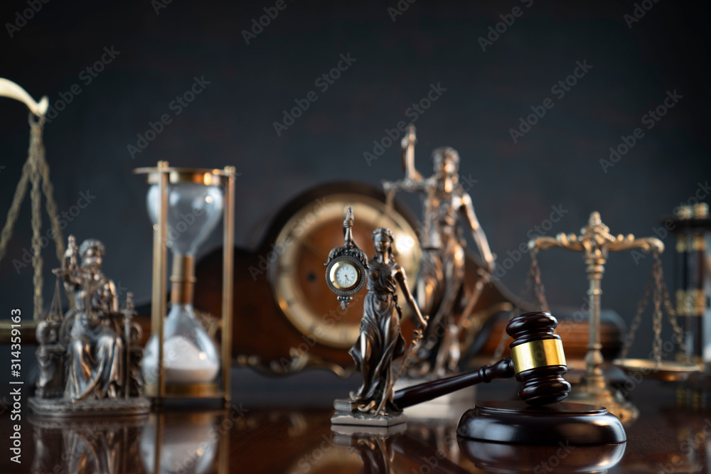 Fototapeta Law and justice theme. Judge's gavel, Themis statue,  scale, hourglass and old clock on the shining wooden brown table and the gray background.