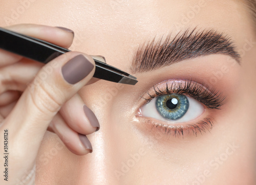 Fotomural  Make-up artist plucks eyebrows with tweezers to a woman with curly brown hair and nude make-up
