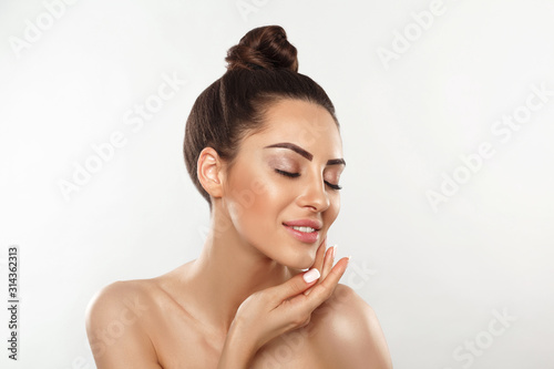 Photo Beautiful smiling woman with healthy smooth facial clean skin applying cosmetic cream and touch own face