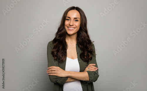 Obraz Mrs. Excellence. Close-up photo of adorable woman, posing in white t-shirts and smiling while looking in the camera. - fototapety do salonu