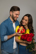 Special day. Close-up photo of a happy man, who is giving his cheerful girlfriend a bouquet of roses and a present in a red heart-shaped box.
