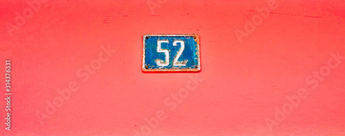 Tela  Number 52, fifty-two, blue plate on vibrant pink background.