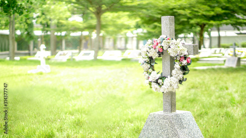 Fotografia Stone cross and grave in graveyard with flare light effect and copy space
