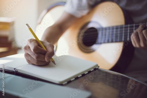 Photo artist songwriter thinking writing notes,lyrics in book at studio