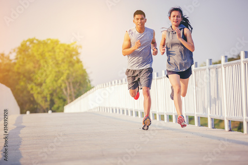 Young couples running sprinting on road. Fit runner fitness runner during outdoor workout