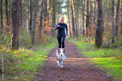 Leinwand Poster Woman jogging in forest with her dog