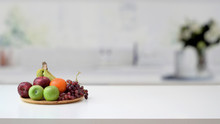 Close Up View Of Fruit Tray And Copy Space On Marble Desk With Blurred Kitchen Room