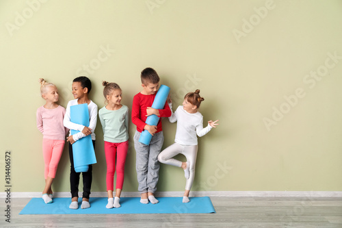 Fotografía Little children with yoga mats near color wall in gym