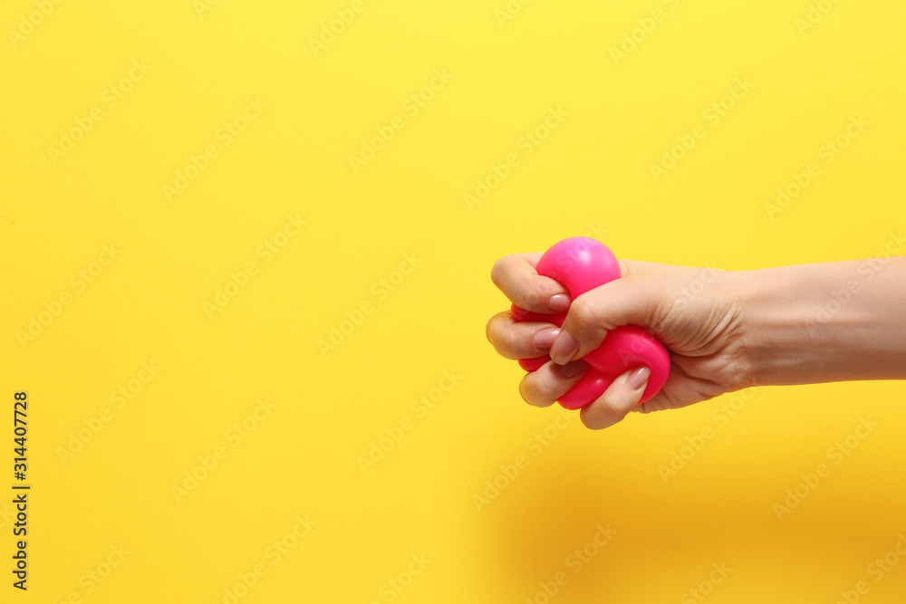 Fototapeta Female hand squeezing stress ball on color background