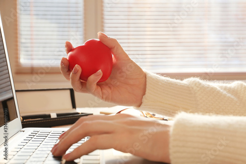 Fotografía  Woman squeezing stress ball while working with laptop in office