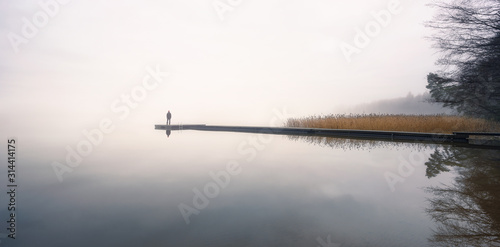 Fotografia Man standing alone on edge of pier and staring at lake