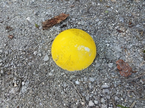 yellow cement sphere in ground with pebbles