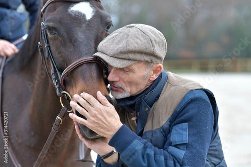 Fototapeta Portrait of horseman standing by horse obraz